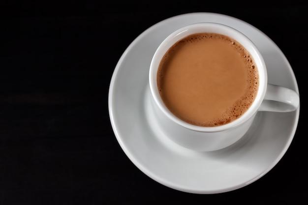 Café com creme em um copo branco sobre uma mesa de madeira preta