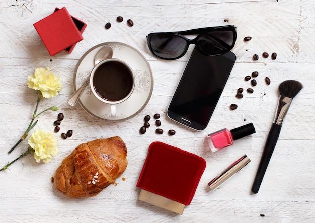 Café com croissant, celular, óculos de sol e maquiagens em uma mesa