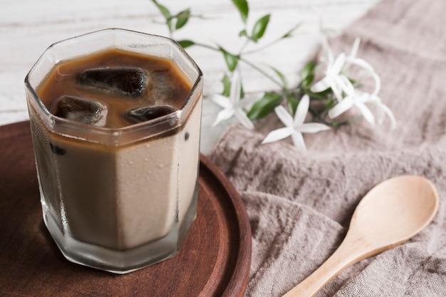 Café com cubos de gelo no copo e flores