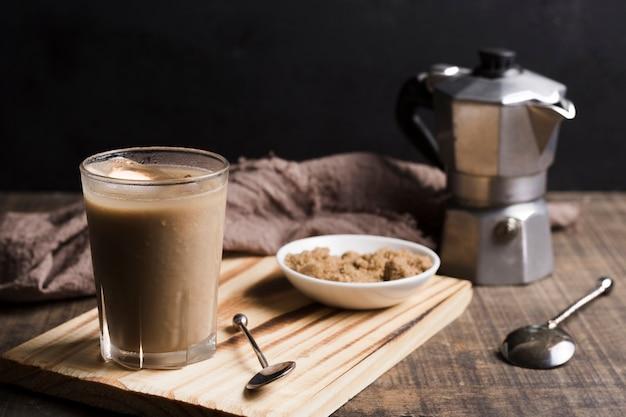 Café com cubos de gelo no copo e moedor