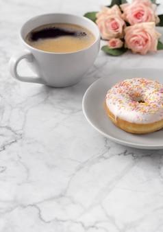 Café com donut colorido em mármore branco