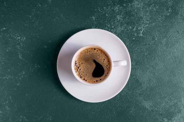 Café com espuma em uma xícara azul na cor da moda de 2021 fundo verde tidewater