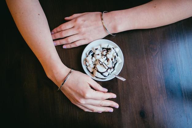 Café com espuma na mesa com as mãos