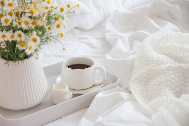 Café com flores em uma bandeja na cama