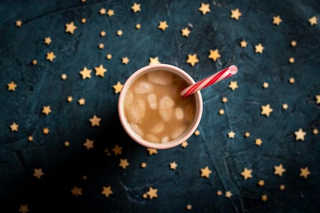 Café com gelo e leite em um copo em um fundo de pedra azul escuro com estrelas. bebida de resfriamento de conceito, sede, verão, céu estrelado, vida noturna, insônia. vista plana, vista superior