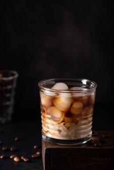 Café com gelo preto com leite em um copo em um fundo preto