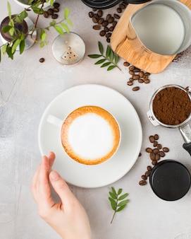 Café com latte art em um copo de cerâmico branco sobre uma mesa