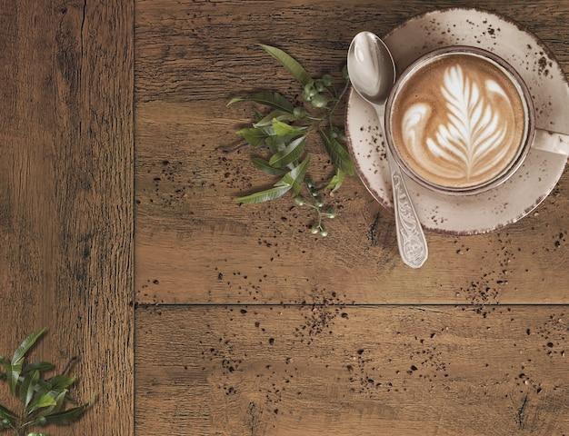 Café com latte art em uma mesa de madeira com grãos de café desintegrados e