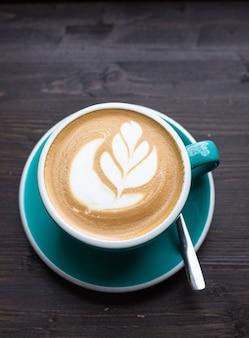 Café com latte art em xícara de cerâmica na mesa de madeira de um café ou cafeteria vista superior