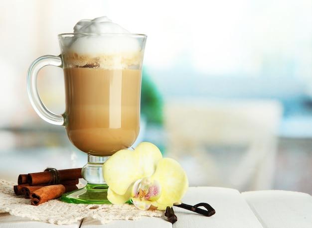 Café com leite aromatizado em copo de vidro com especiarias, na mesa de madeira
