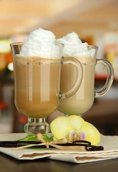 Café com leite aromatizado em xícaras de copos com vagens de baunilha, na mesa do café