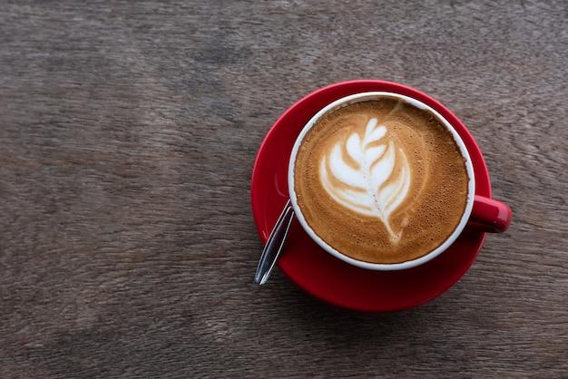 Café com leite arte na mesa de madeira, vista superior