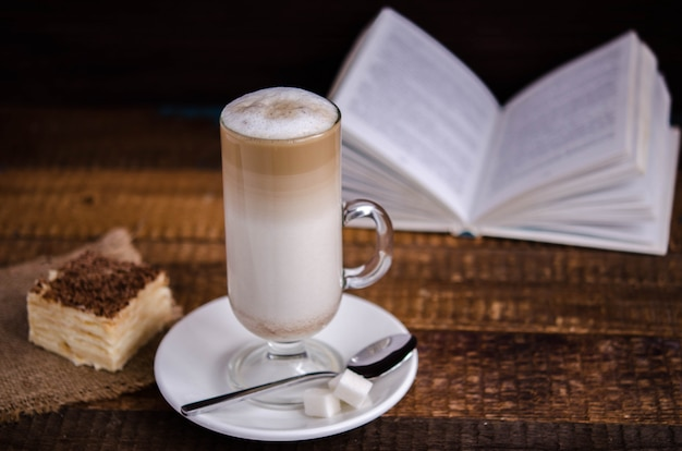 Café com leite beber em um copo de vidro com um livro em segundo plano
