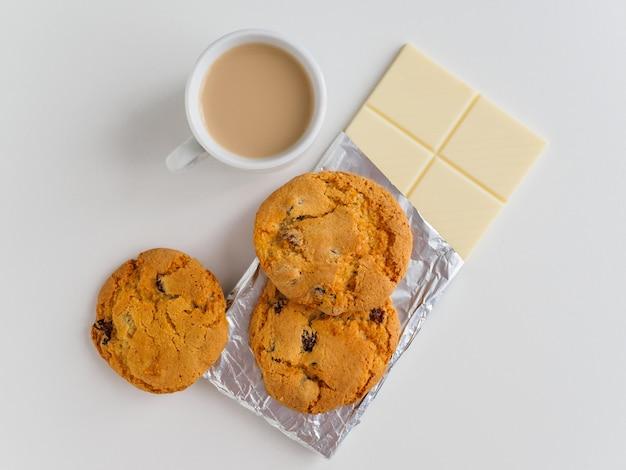Café com leite, biscoitos e chocolate branco.