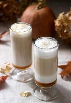 Café com leite caseiro de abóbora em copos altos e abóbora numa toalha de mesa de linho. estilo rústico.