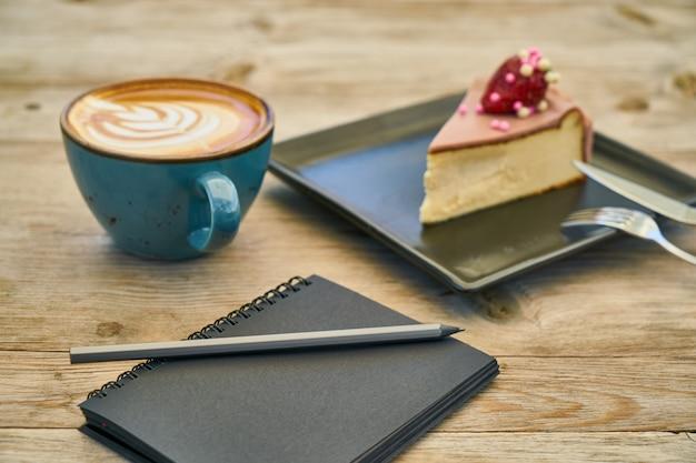 Café com leite, cheesecake e notebook na mesa