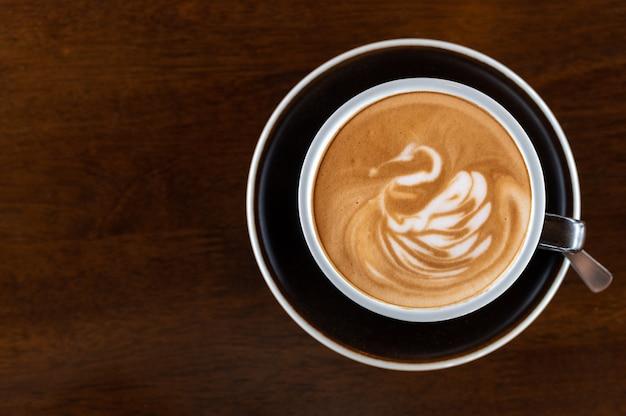 Café com leite com arte de cisne em copo preto na mesa de madeira
