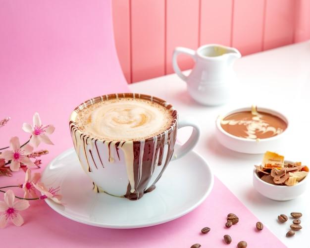 Café com leite com choco café com calda de chocolate e chocolate na mesa