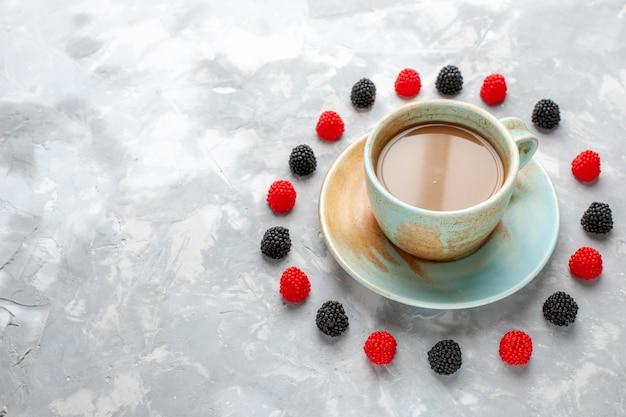 Café com leite com confitures de frutas vermelhas na mesa branca
