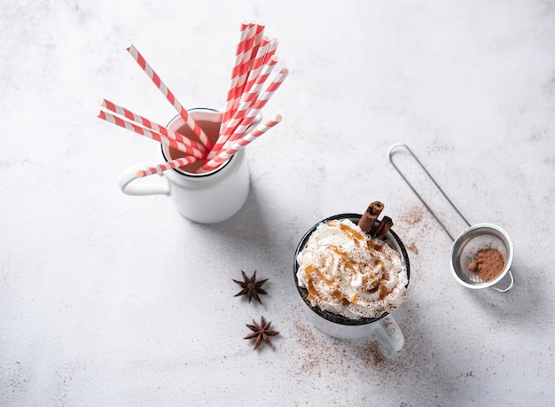 Café com leite com creme de caramelo, tubo de papel vermelho e canela em uma caneca branca sobre uma mesa branca