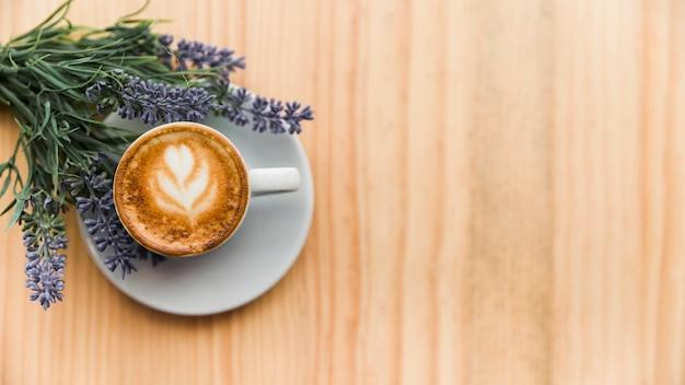 Café com leite com flor de lavanda na superfície de madeira