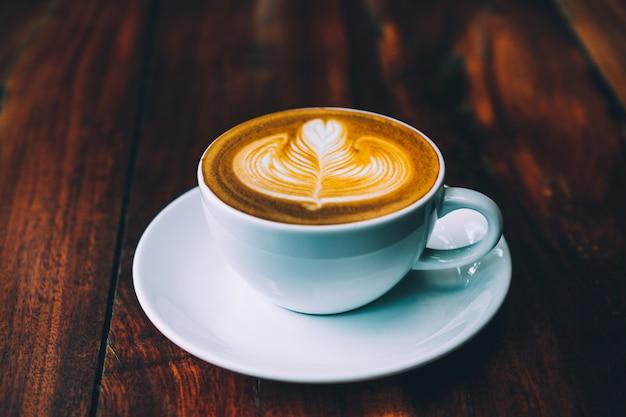 Café com leite com leite na mesa de madeira na cafeteria para beber na hora do café