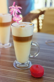 Café com leite com macaroon na mesa na rua, terraço, café ao ar livre, pôr do sol