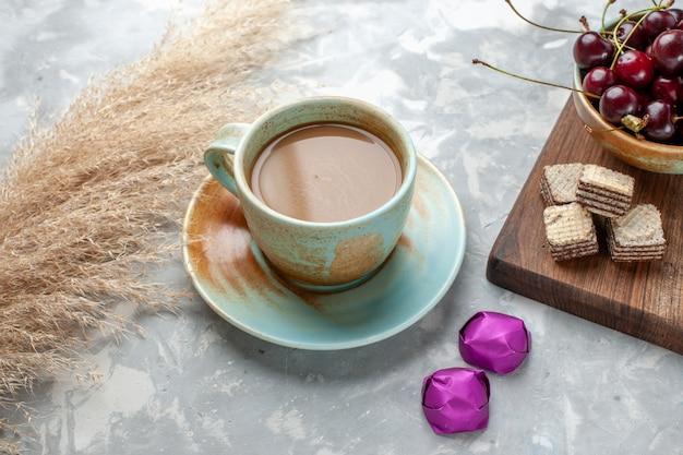 Café com leite com waffles de doces e cerejas ácidas na luz