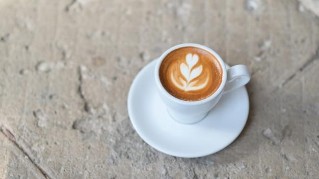 Café com leite coração textura na mesa de concreto.