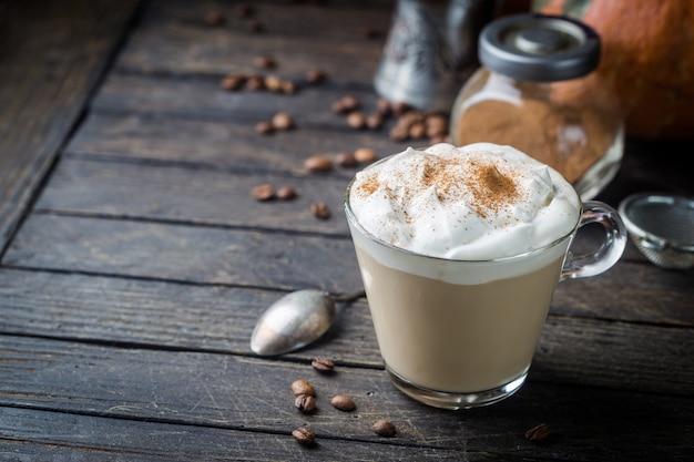 Café com leite de abóbora com chantilly e especiarias, com abóboras sobre textura de madeira.