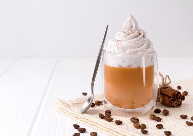 Café com leite de abóbora com chantilly e especiarias na mesa de madeira branca