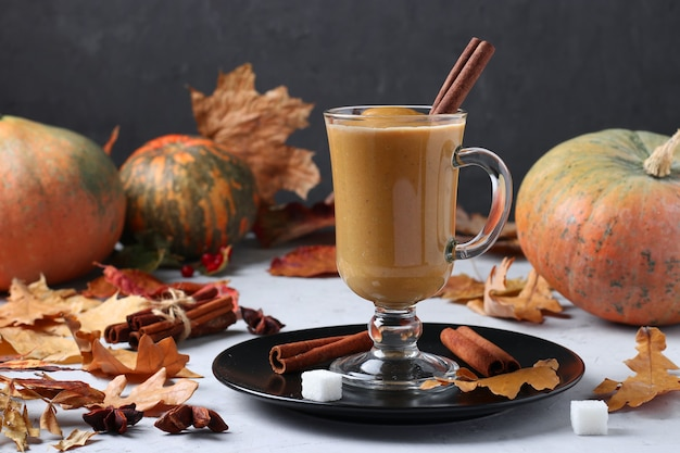 Café com leite de abóbora com especiarias em um copo de vidro em um fundo escuro com abóboras e folhas de outono, close-up. formato horizontal.