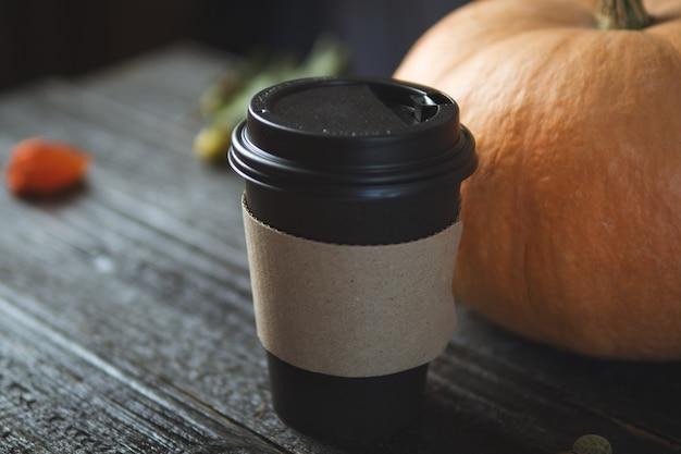 Café com leite de abóbora em um copo de papel café com ele em uma mesa de madeira