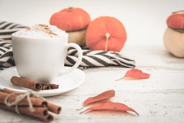 Café com leite de abóbora picante, copo branco de bebida quente de outono, com abóboras, canela e especiarias