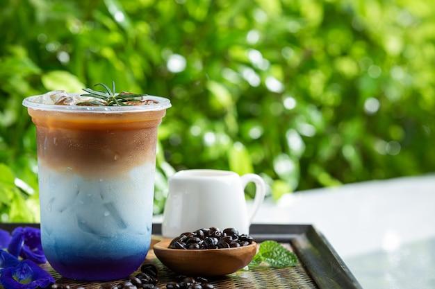 Café com leite de ervilha borboleta gelada em superfície de madeira