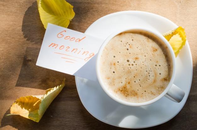 Café com leite e a inscrição bom dia.