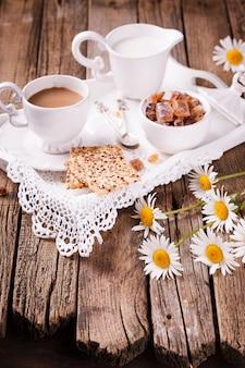 Café com leite e biscoitos em uma bandeja.