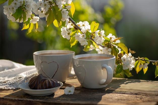 Café com leite e cacau chá em xícaras com guardanapo de renda decorado com coração em mesa de madeira