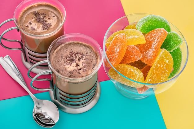 Café com leite e doces de canela de geléia em uma barra de vidro em uma superfície brilhante