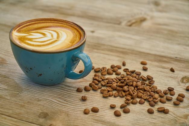 Café com leite e grãos de café na mesa de madeira