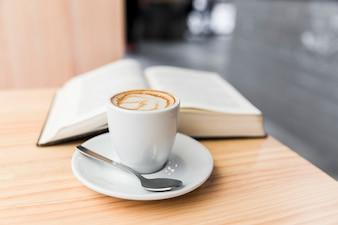 Café com leite e livro aberto na mesa de madeira