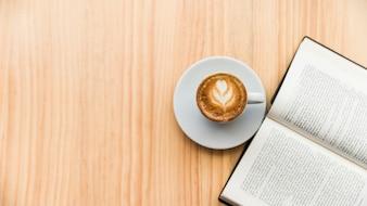 Café com leite e livro aberto na superfície de madeira