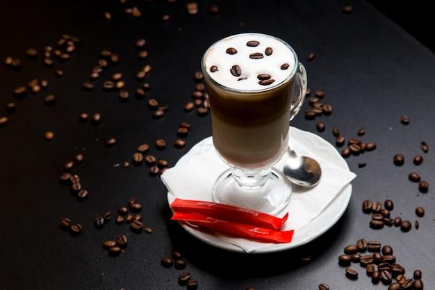 Café com leite em cima da mesa com vista lateral para colher de açúcar de feijão