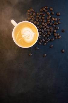 Café com leite em close-up na xícara e espuma de leite acima para beber na superfície posterior