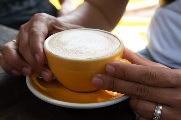 Café com leite em copo amarelo com as mãos do homem