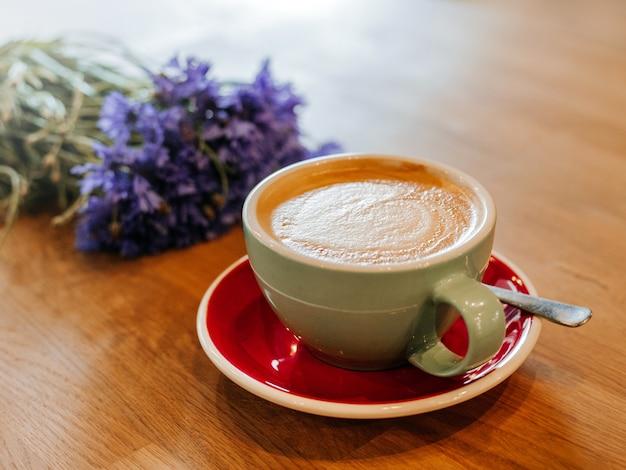 Café com leite em mesa de madeira com flor centáurea em efeito de filtro de filme retrô