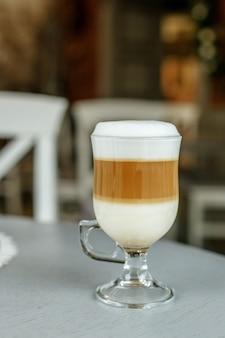 Café com leite em um copo de vidro.