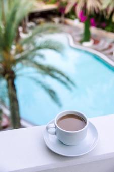 Café com leite em uma xícara branca na varanda do hotel.