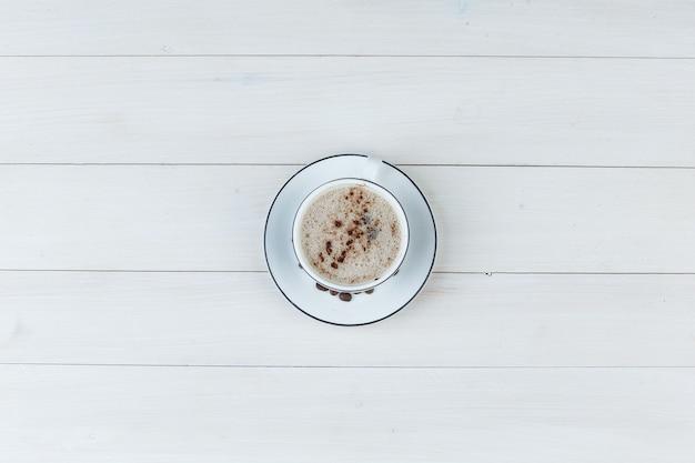 Café com leite em uma xícara em um fundo de madeira. vista do topo.