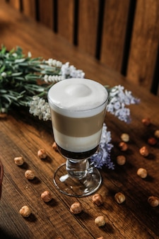 Café com leite, espuma de leite, nozes